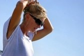 5466001-a-beautiful-blonde-woman-outsdie-at-the-beach-is-fixing-her-hair-wearing-sunglasses-large-hoop-earrr